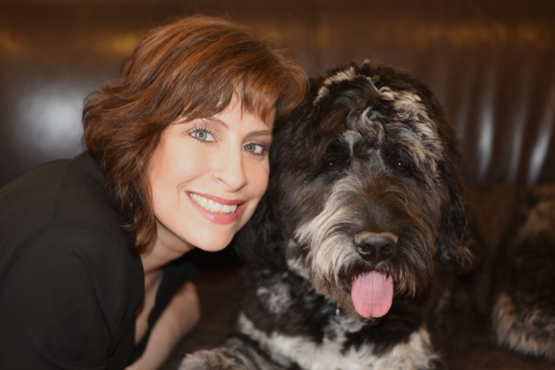 Brown haired smiling woman next to happy looking dog with tongue out.
