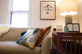 Office space showing couch with pillows and art on wall