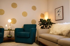 Office space with cream couch and teal armchair, with gold circle decoration on the wall