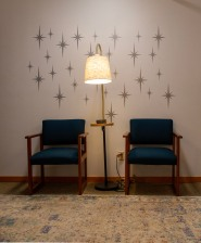 Waiting area with two teal chairs, lamp, and starburst designs on the wall
