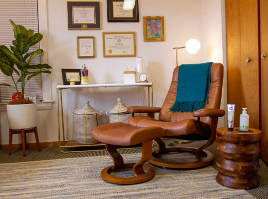 Office space with brown chair and art on wall